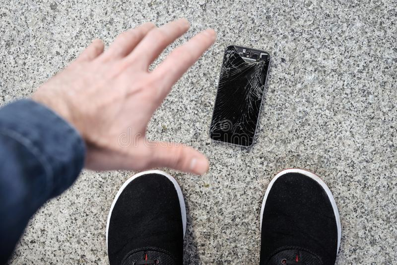 Upset young man sits and holds a broken smartphone with a cracked glass screen. Copy space royalty free stock image