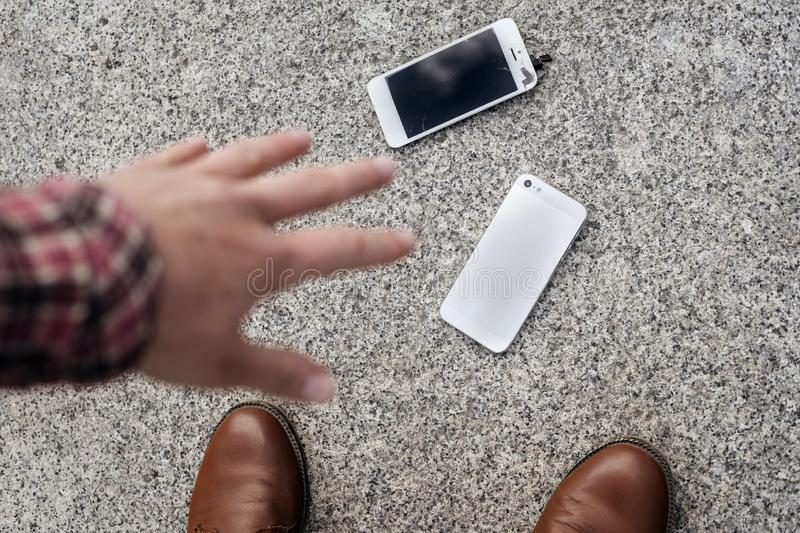 Upset young man sits and holds a broken smartphone with a cracked glass screen. Copy space stock photo