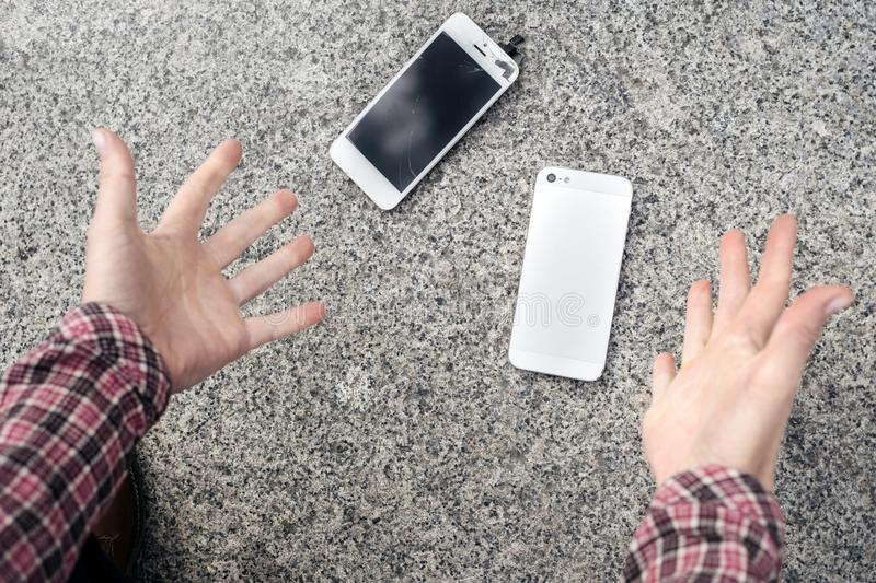 Upset young man sits and holds a broken smartphone with a cracked glass screen. Copy space royalty free stock photography