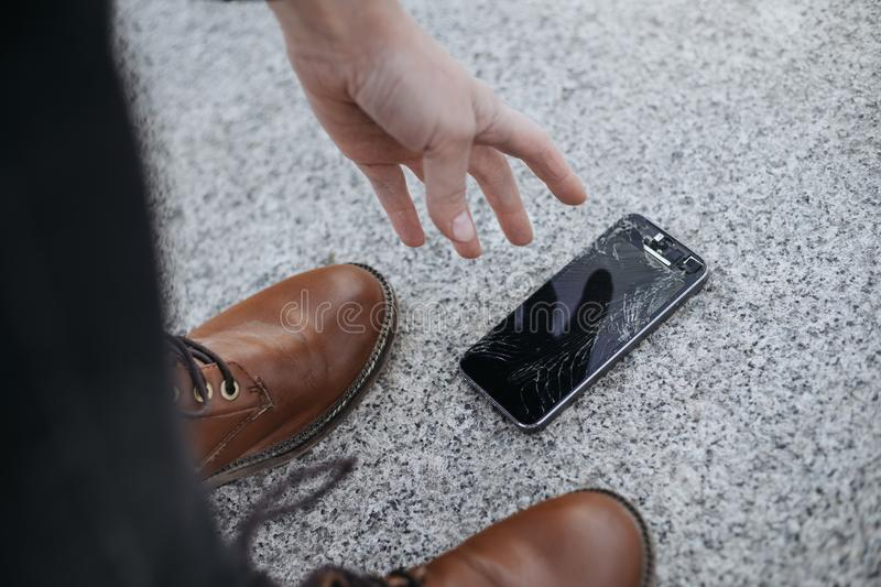 Upset young man sits and holds a broken smartphone with a cracked glass screen. Copy space stock images