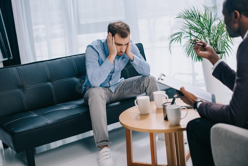 Upset young man sitting on couch and psychiatrist. Upset young men sitting on couch and psychiatrist with clipboard stock images
