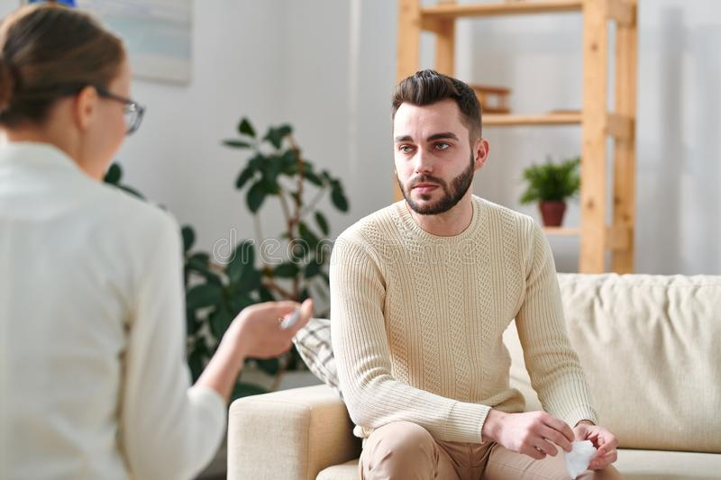 Listening to advice. Upset young men in casualwear sitting on couch in front of counselor and listening to her advice during individual session stock photography