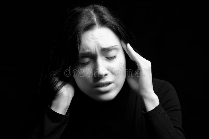 Upset young woman. Black and white portrait of upset young woman holding head in hands, black background stock image