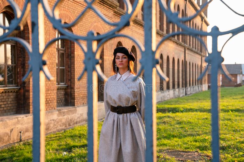 Upset young woman in black beret and grey dress stands near the old brick wall behind the old forged fence royalty free stock photos