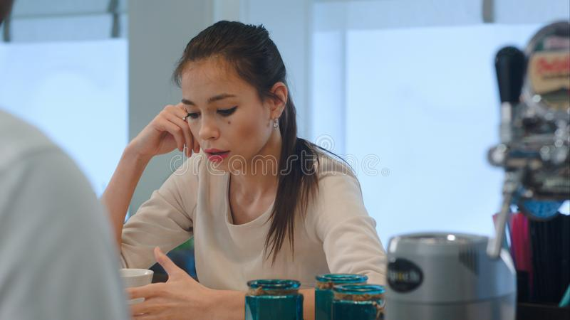 Upset young woman complaining to the barista at bar counter in cafe stock images