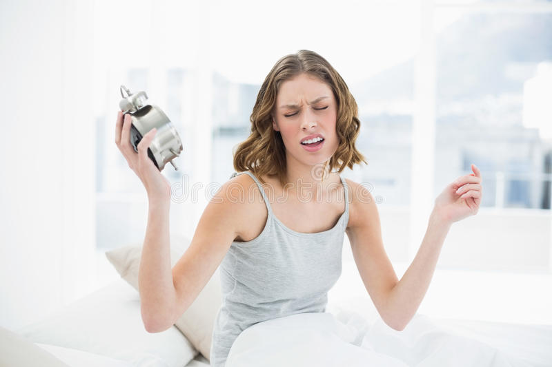 Upset young woman holding an alarm clock sitting on her bed royalty free stock image