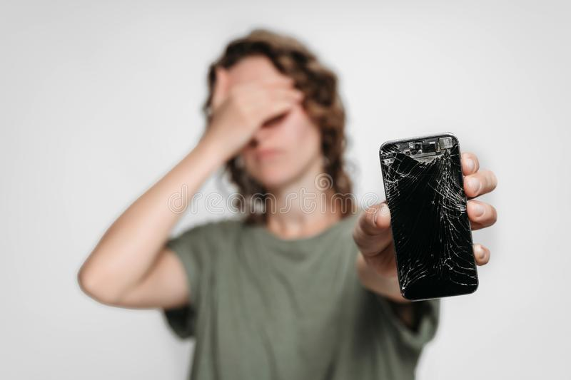 Upset young woman holding her broken smartphone. Phone screen need to repair. Isolated on gray background royalty free stock photo
