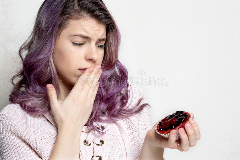 Upset young model holding sweet dessert with berries. Space for text stock image