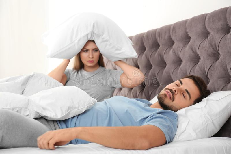 Upset young woman sitting on bed  her sleeping husband at home. Relationship problems stock photos