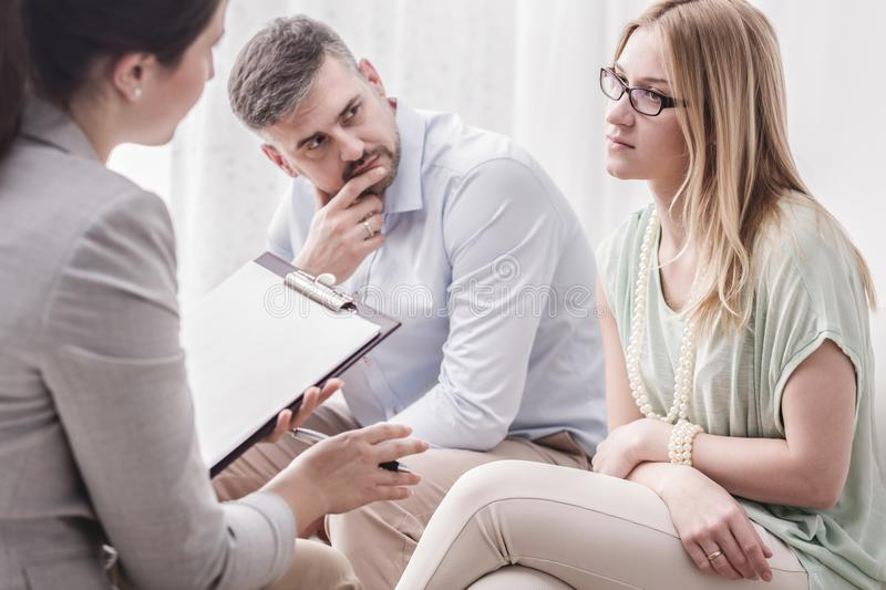 Woman talking to psychologist. Upset young women talking to a female psychologist, with her husband by her side during marital counseling stock photography