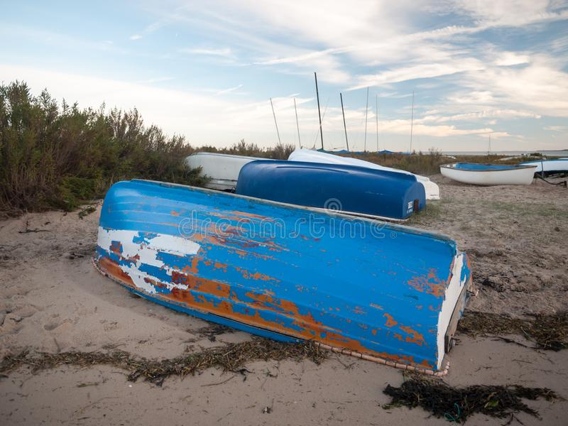 Upside down blue chipped painted private boat moored on beach. West mersea, essex, england, uk royalty free stock image