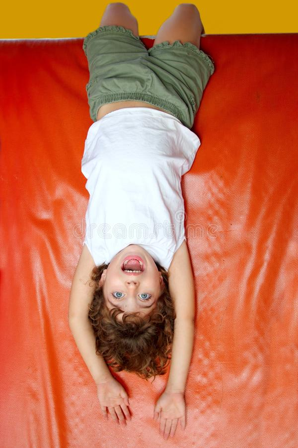 Upside down little girl on slide laughing royalty free stock images