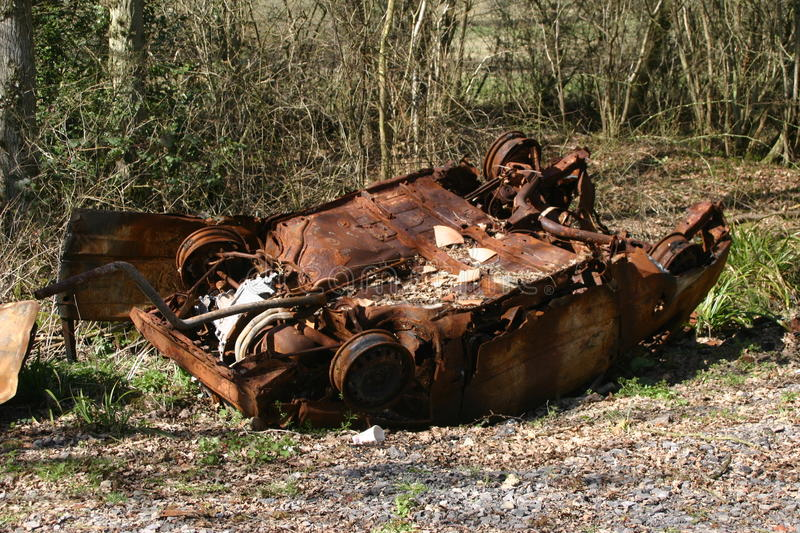 Upside down rusting car in a wood. Derelict abandoned upside down rusting car in a wood royalty free stock photo