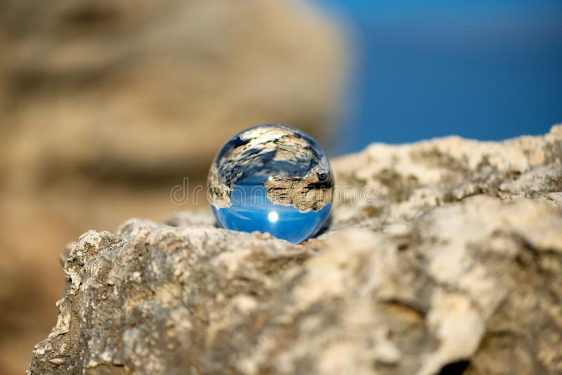 Upside down seascape with blue sky and overgrown with moss rocks - reflection in a lens ball royalty free stock photos