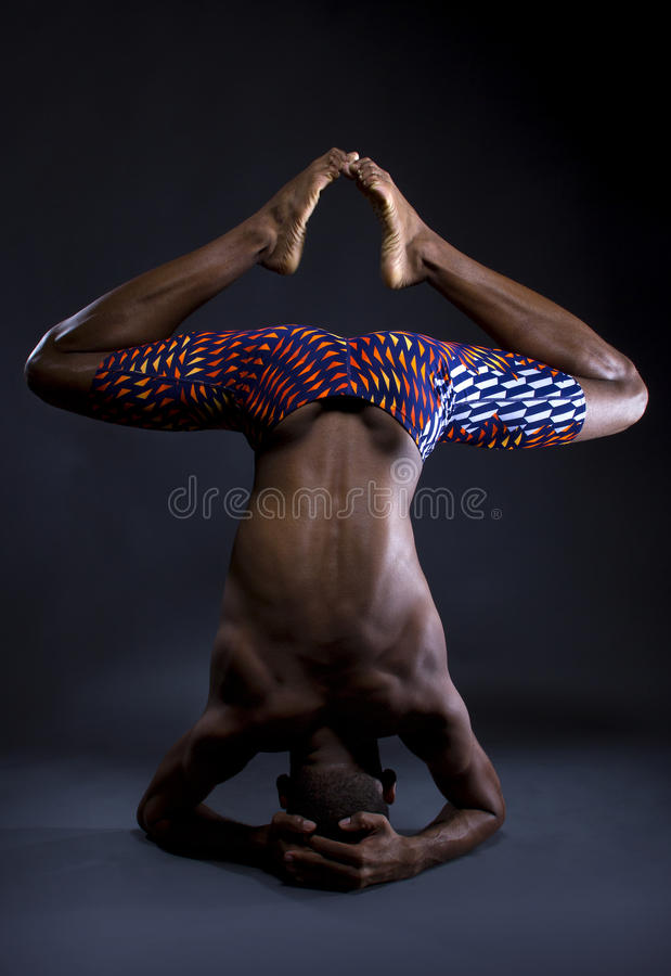 Upside Down Yoga. Muscular black man doing upside down yoga on grey background royalty free stock image