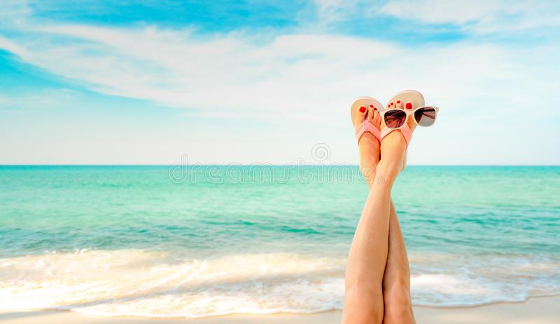 Upside woman feet and red pedicure wear pink sandals, sunglasses at seaside. Funny and happy fashion young woman relax on vacation. Girl on beach. Creative for stock photos