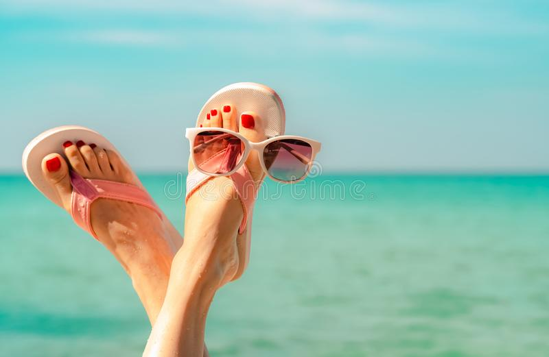 Upside woman feet and red pedicure wearing pink sandals, sunglasses at seaside. Funny and happy fashion young woman relax. On vacation. Chill out girl at beach royalty free stock photo