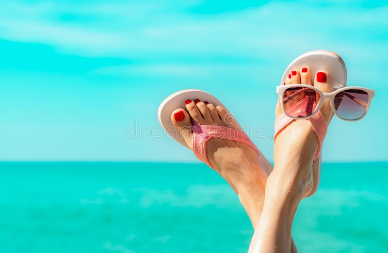 Upside woman feet and red pedicure wearing pink sandals, sunglasses at seaside. Funny and happy fashion young woman relax. On vacation. Chill out girl at beach stock images