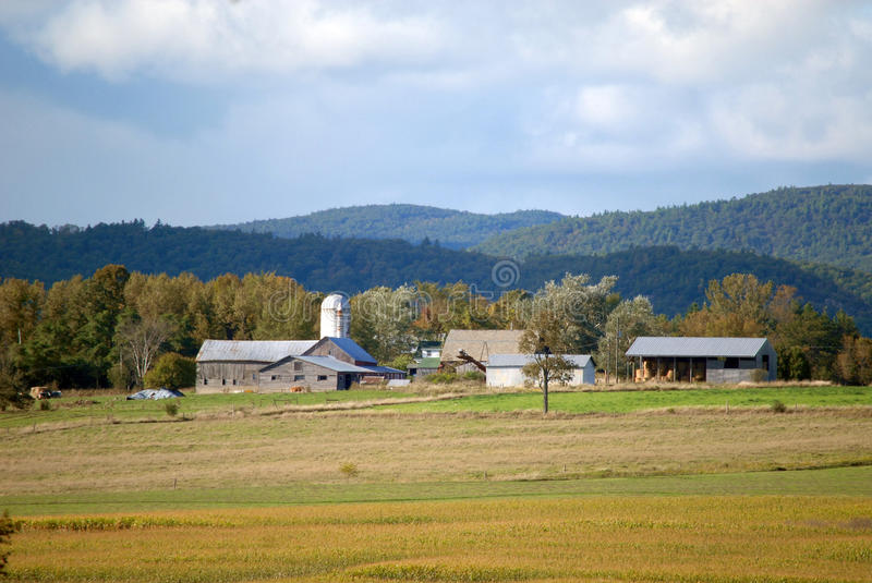 Upstate New York farm buildings with background of tall trees, mountains, and Blue skies royalty free stock photography