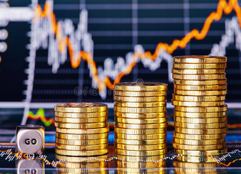 Uptrend stacks coins, dices cube with the word GO. On the financial stock charts as background. Selective focus stock photos