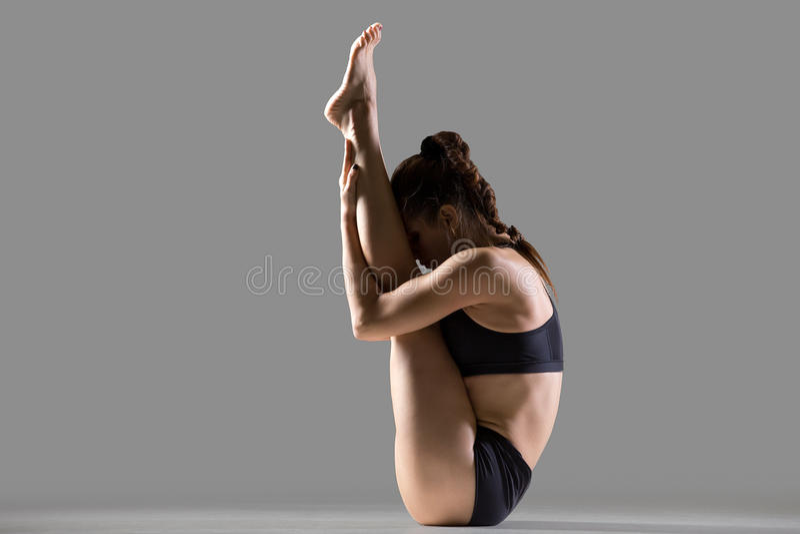 Upward Facing Forward Bend. Portrait of beautiful young fit woman in sportswear doing sport exercise, sitting in upward facing forward bend posture (urdhva mukha stock photography