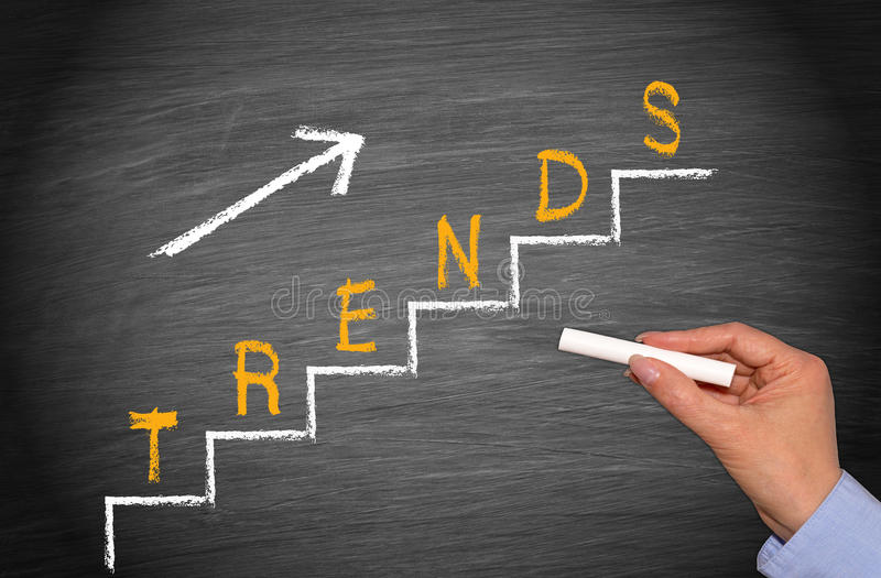 Upward trends illustration. Female hand holding white chalk next to blackboard illustrated with steps and upward arrow in white and yellow text graphics trend stock photo