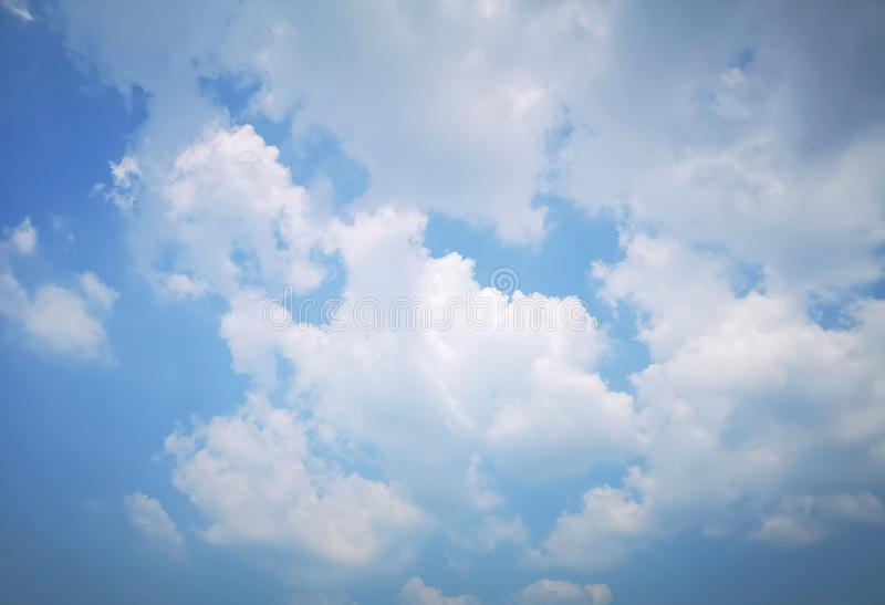 Upward view beautiful white fluffy clouds on vivid blue sky in a suny day. For background stock photography