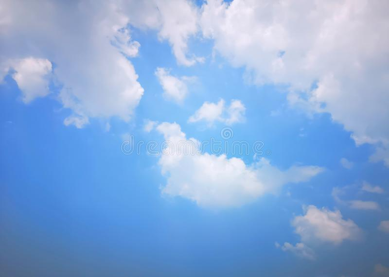 Upward view beautiful white fluffy clouds on vivid blue sky in a suny day. For background royalty free stock photo