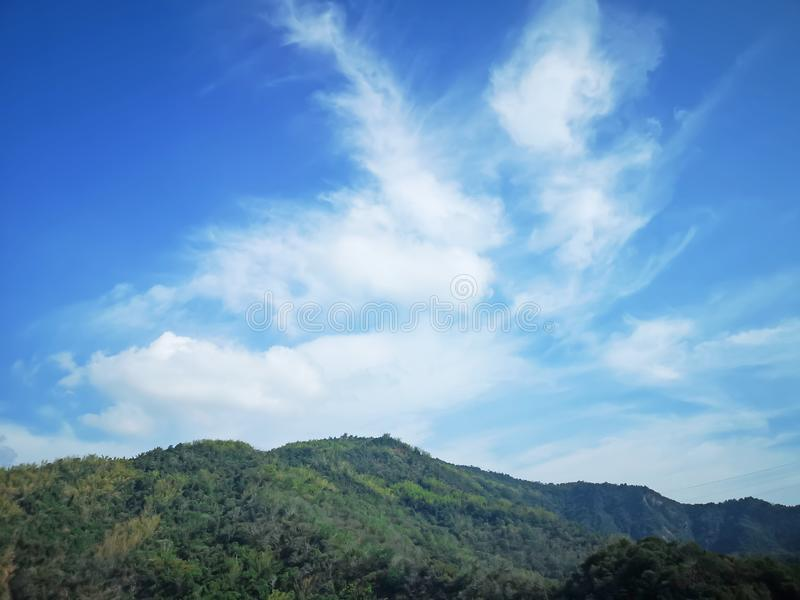 Upward view beautiful white fluffy clouds on vivid blue sky in a suny day above greenery mountain. Upward view beautiful white fluffy clouds on vivid blue sky in royalty free stock photo