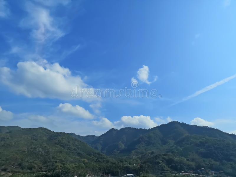 Upward view beautiful white fluffy clouds on vivid blue sky in a suny day above greenery mountain. For background stock image