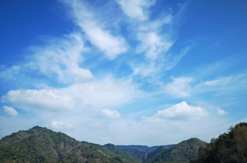 Upward view beautiful white fluffy clouds on vivid blue sky in a suny day above greenery mountain. For background stock photo