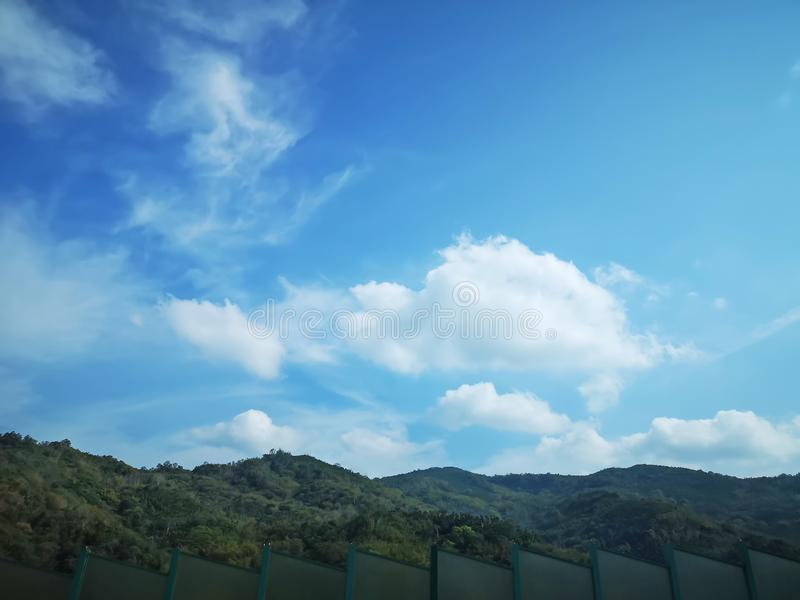 Upward view beautiful white fluffy clouds on vivid blue sky in a suny day above greenery mountain and green wall. Upward view beautiful white fluffy clouds on stock photo
