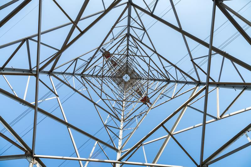 Upward view of electricity pylon. High voltage pylon on blue sky background, upward view of transmission line tower royalty free stock photography