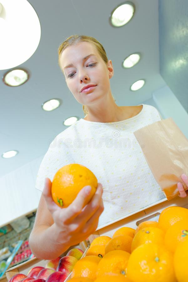 Upward view lady in shop buying oranges. Upward view of lady in shop buying oranges royalty free stock photo
