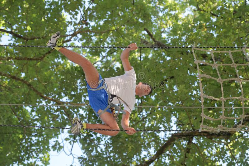 Upward view man crawling across rope bridge. Upward view of man crawling across rope bridge stock photos