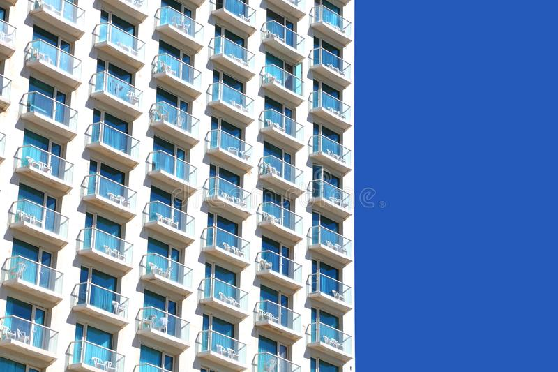 Balconies of modern hotel. Upward View on Modern Building. Balconies of modern hotel. Bright blue sky background stock images