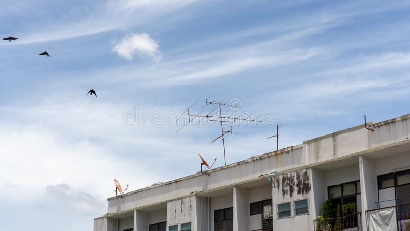 Upward view of old building under beautiful white fluffy cloud formation on vivid blue sky in a sunny day. Telephone and television antenna on the rooftop royalty free stock images