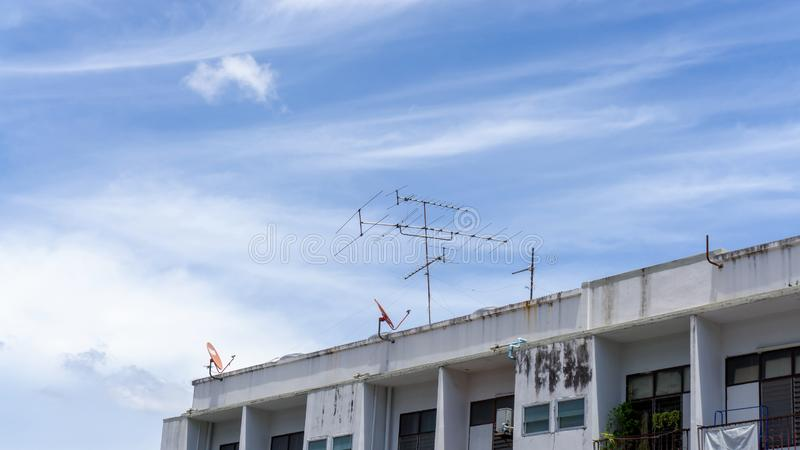 Upward view of old building under beautiful white fluffy cloud formation on vivid blue sky in a sunny day. Telephone and television antenna on the rooftop stock photography