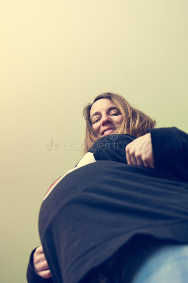 Upward view of pregnant belly. Expecting mother smiling royalty free stock photo