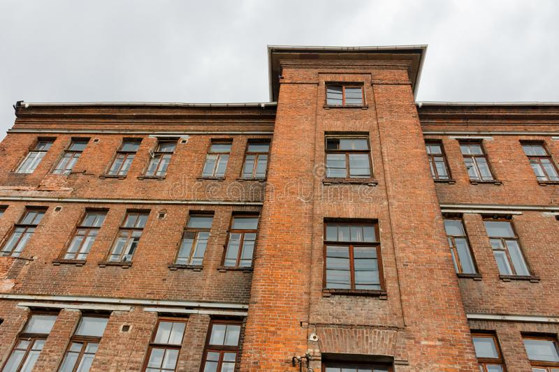 Upward view to old red brick wall building with windows and cloudy sky on the background stock images
