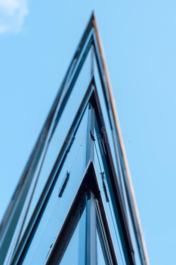 View at top of modern office building with glass and steel under blue sky, reflections and selective focus. stock image