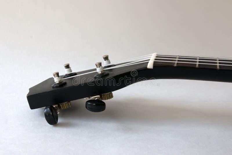 Uquelele, guitarra pequena preta, em um fundo branco fotos de stock royalty free