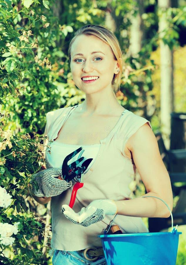 Uradowana kobieta ma ogrodniczych instrumenty w ogródzie zdjęcie royalty free