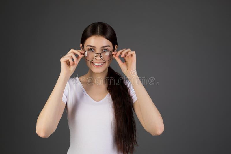 Uradowana szczęśliwa brunetki kobieta jest ubranym białą koszulkę, ono uśmiecha się szeroko obraz stock
