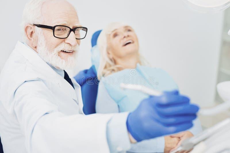 Uradowany męski dentysta chwyta instrument zdjęcie stock