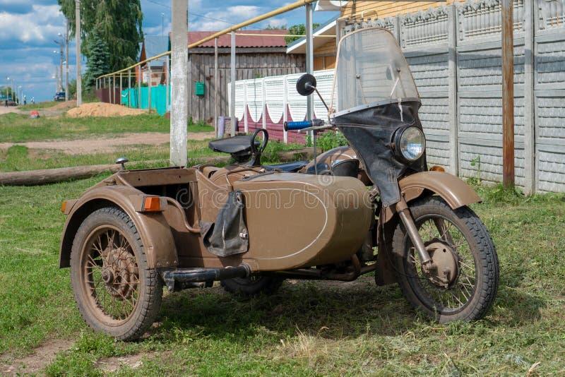 Ural moped med sidecaren Ural är ett ryskt märke av tunga sidecarmotorcyklar som göras ursprungligen i Sovjetunionenet royaltyfria foton