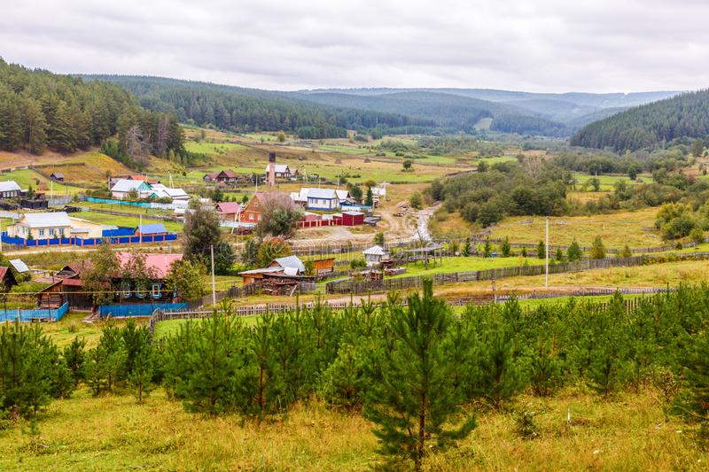 A fragment of the South Ural village. Ural village among the mountain peaks and taiga. A fragment of the South Ural village stock photo