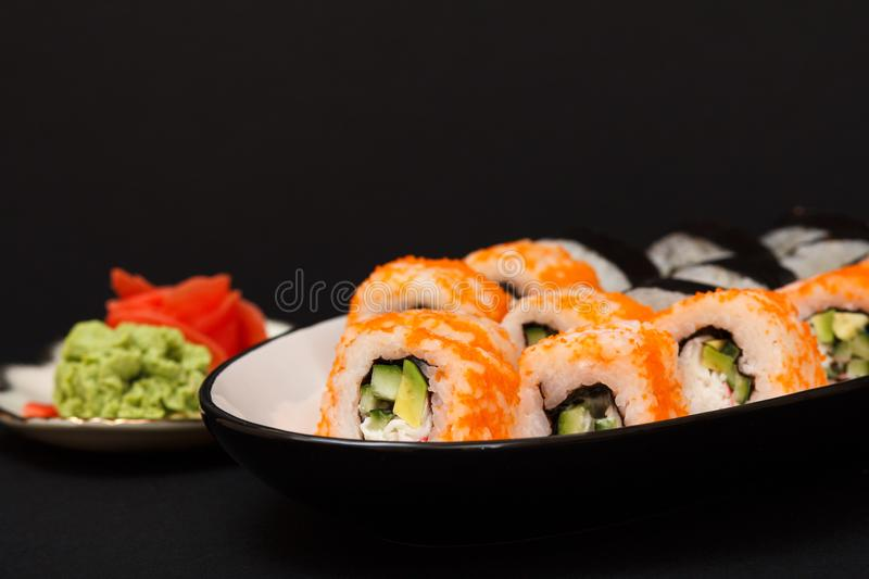 Uramaki California. Sushi rolls, plate with red pickled ginger and wasabi royalty free stock photo