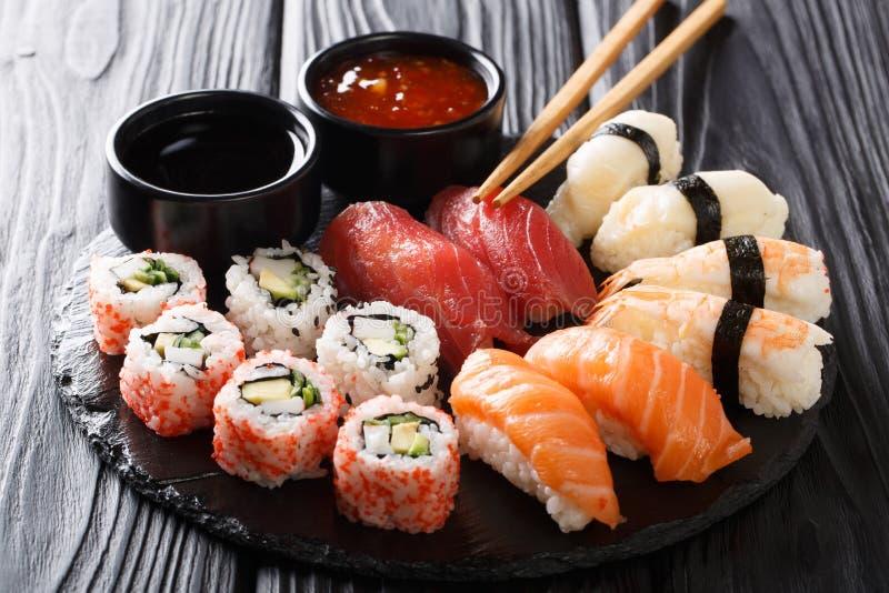 Uramaki and nigiri sushi served in black plate closeup. horizontal stock photo
