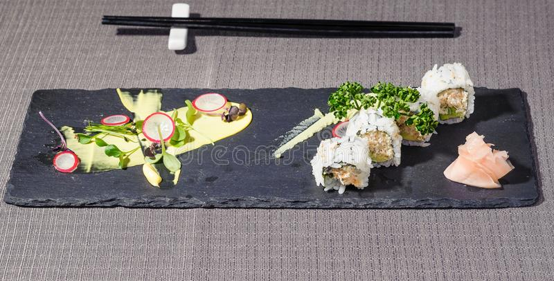Uramaki rool with cheese and vegetables, japponese cuisine revisited. Served on a rectangular blackboard dish royalty free stock photography